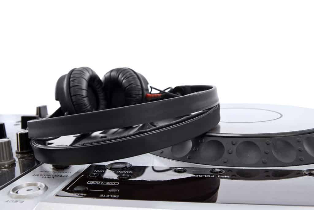 Photo of a pair of headphones sitting on a DJ controller