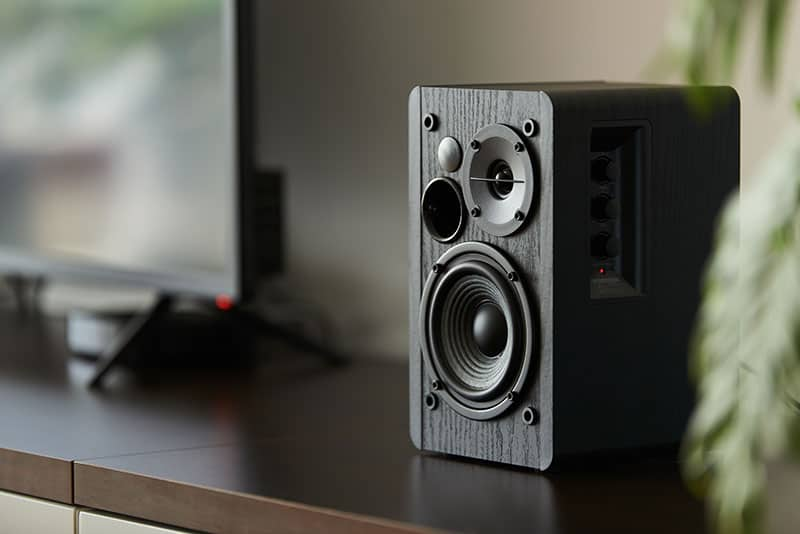 Bookshelf speaker sitting next to a TV.