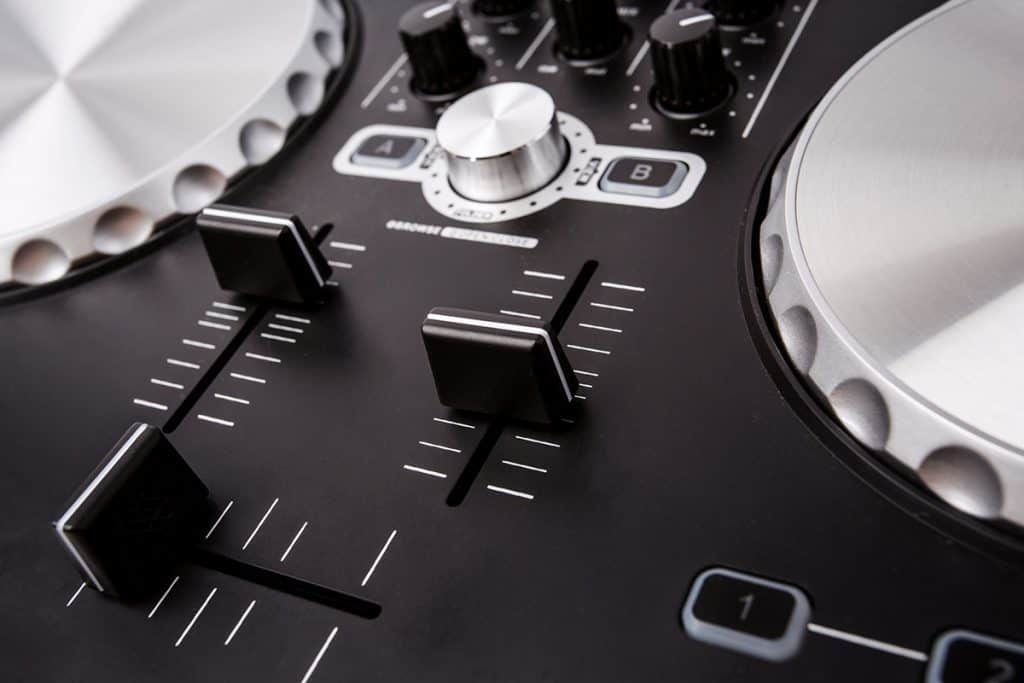 A close up picture of the crossfader and channel faders on a DJ controller.