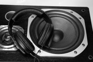 Headphones sitting on top of a speaker.