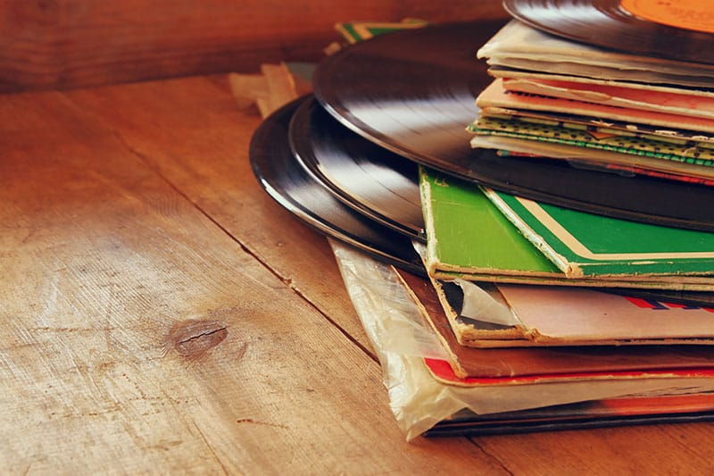 Pile of vinyl records sitting on a wooden table.
