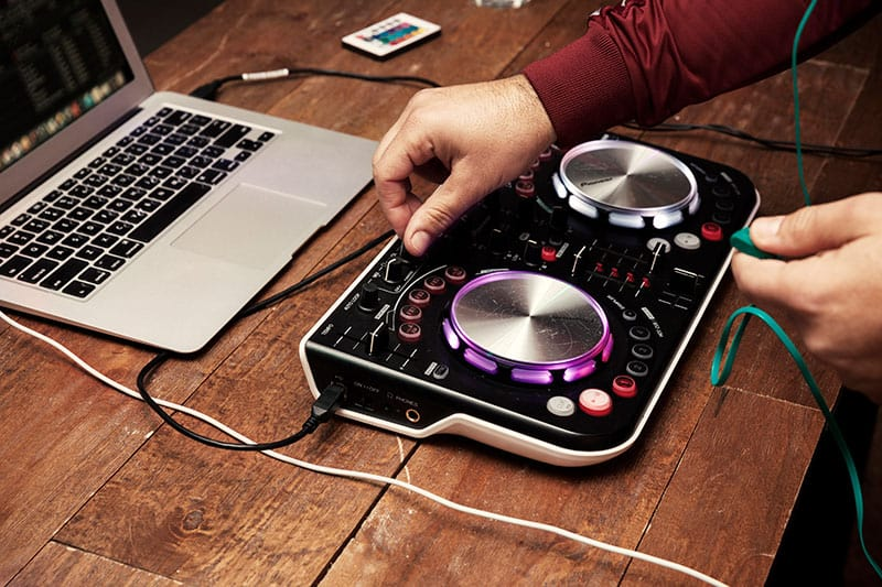 A photo of a DJ mixing on an entry-level controller.