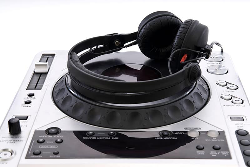 DJ Headphones sitting on top of a DJ mixer.
