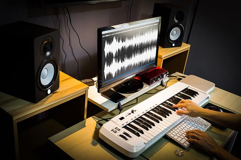 Studio Monitors sitting next to a computer screen with a MIDI keyboard in front