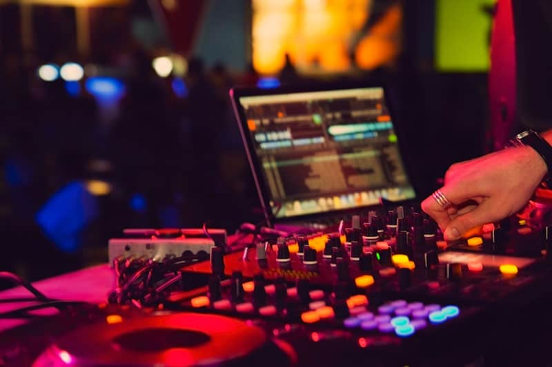 DJ performing on DJ equipment with a laptop in the background.