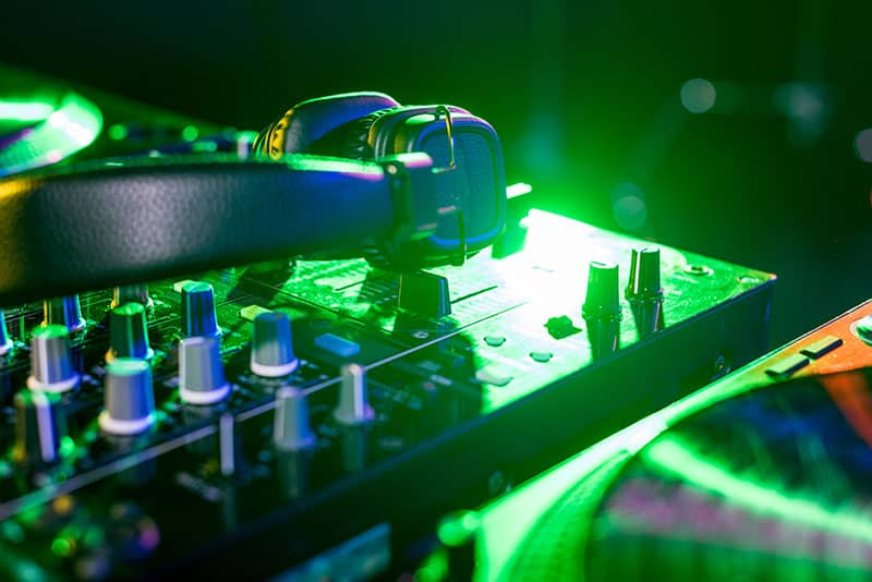 Photo of headphones sitting on top of a DJ controller