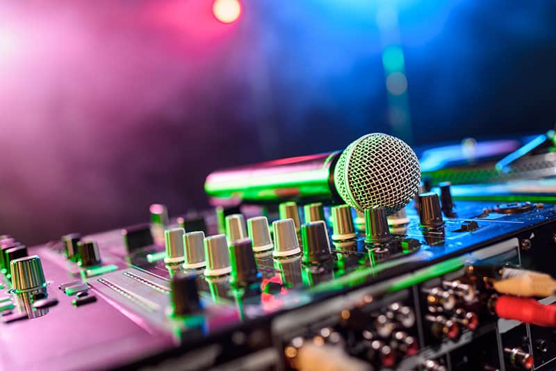 Photo of a microphone sitting on top of a DJ mixer.