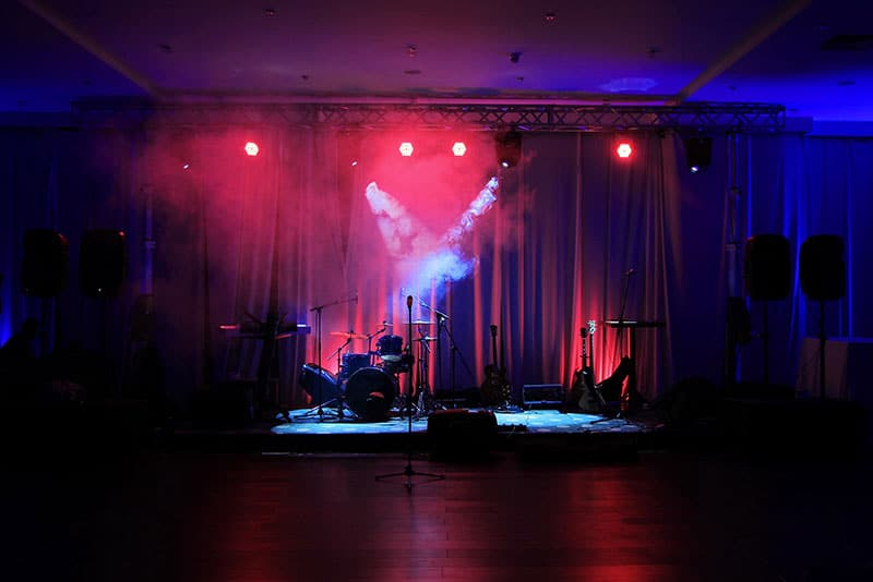 Photo of a stage with instruments, speakers and lighting.