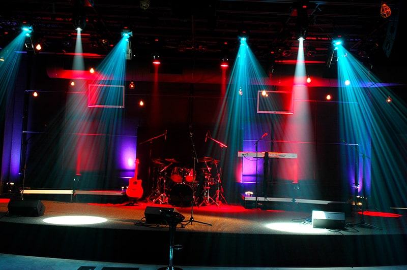 Photo of a stage with musical instruments and speakers.