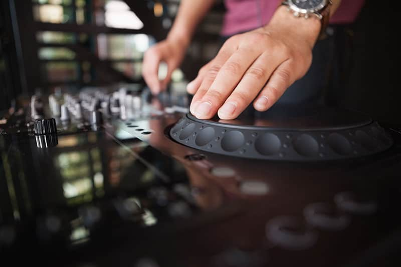 Close Up photo of a DJ using a jogwheel.