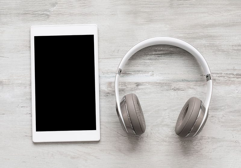 Tablet and headphones on a wooden background