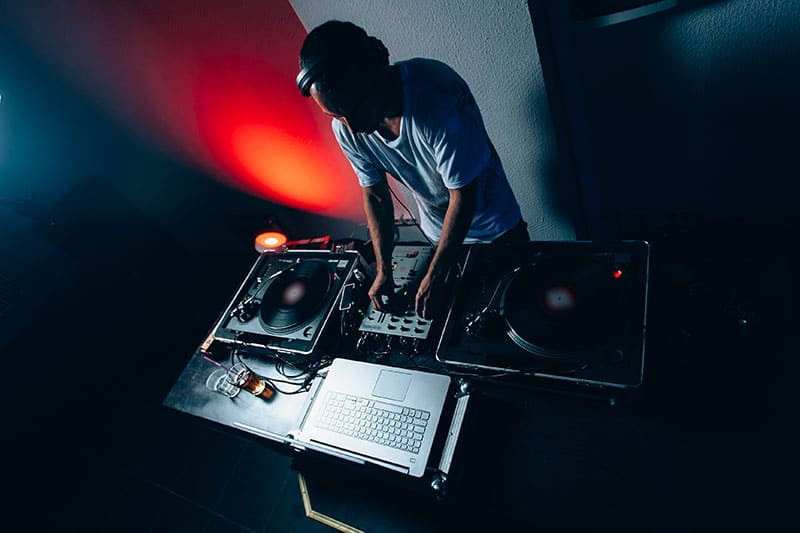 DJ in front of DJ equipment and a laptop