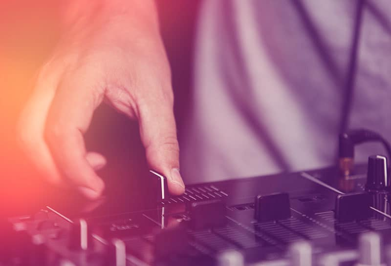 DJing using a crossfader on a DJ controller.