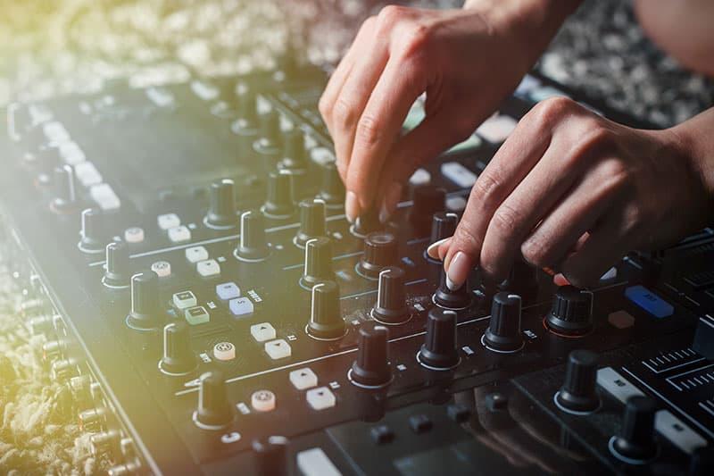 DJ altering the EQ on a DJ mixer.