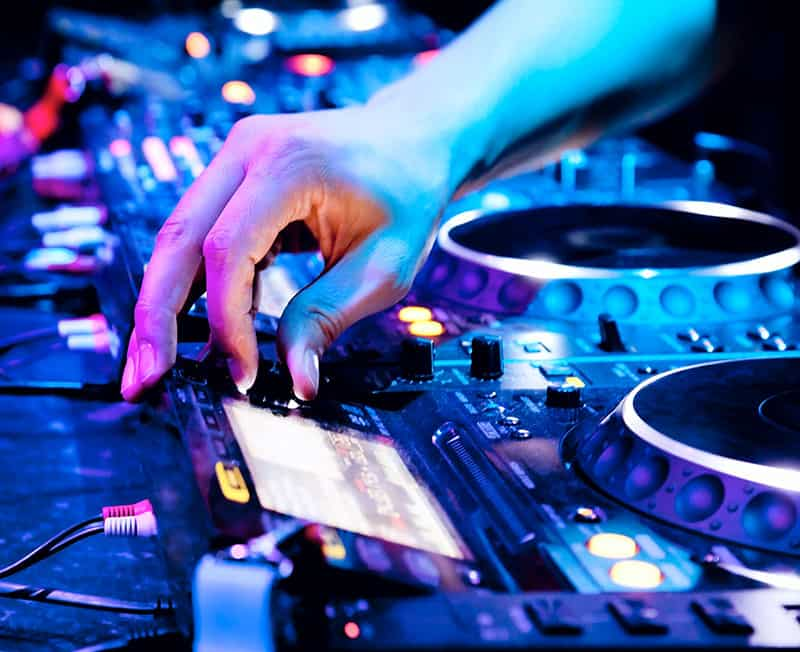DJ selecting a song on a screen on DJ gear