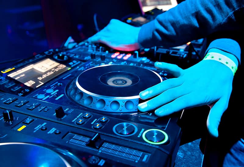 DJ playing music on professional equipment.