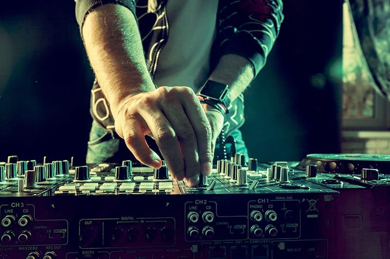 DJ adjusting EQ knobs on professional DJ gear