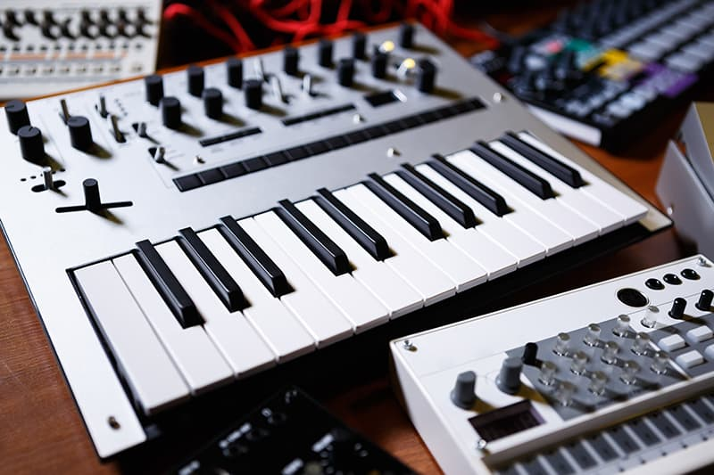 Various pieces of music gear like keyboards and synths.
