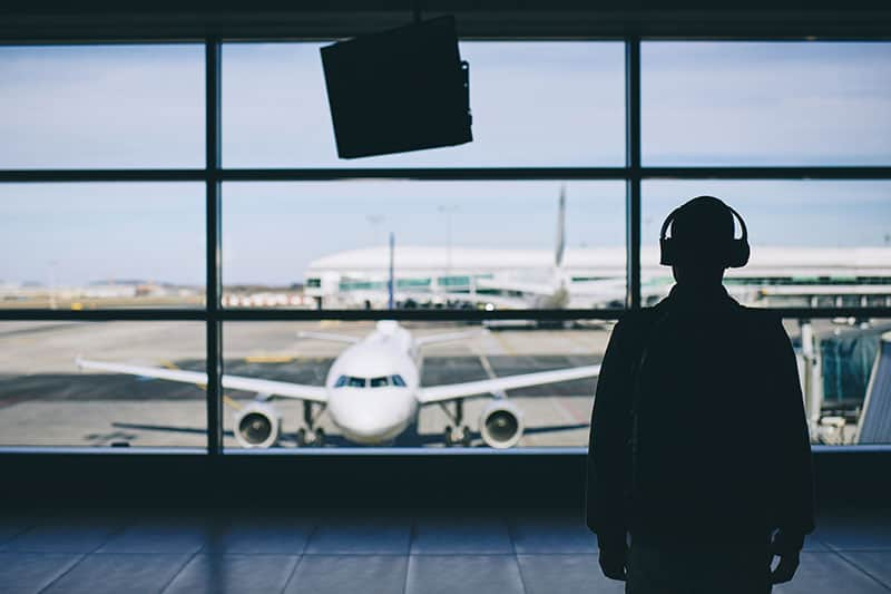 Silhouette of a man with headphones at an airport