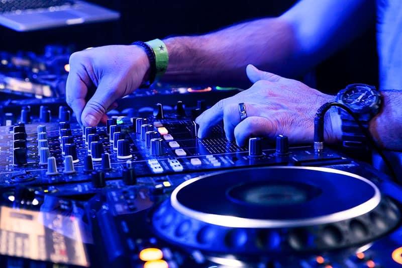 DJ using Pioneer Dj equipment in a club.