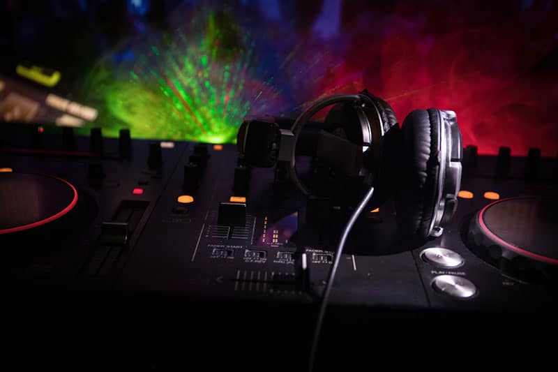 Headphones sitting on Dj equipment with a dark background